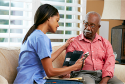 caregiver getting the blood pressure of the elderly man